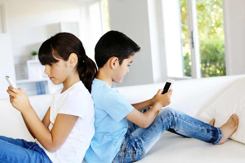 14663622 - kids playing at home with smartphones