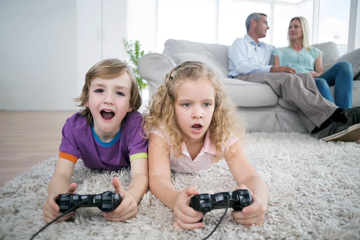 38145085 - brother and sister playing video game while parents sitting on sofa at home