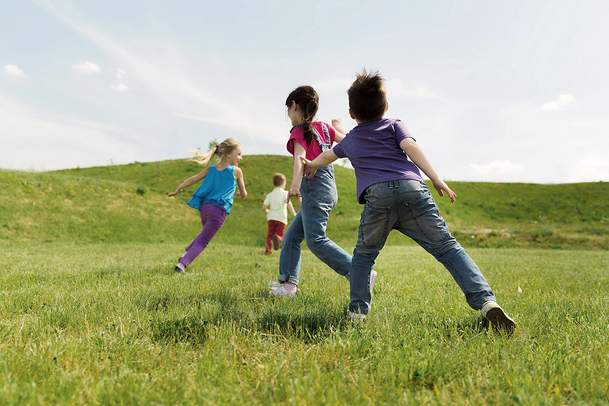 54718073 - summer, childhood, leisure and people concept - group of happy kids playing tag game and running on green field outdoors