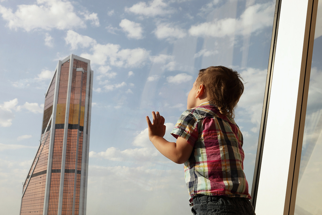 Kid looking at skyscrapers from penthouse in Moscow