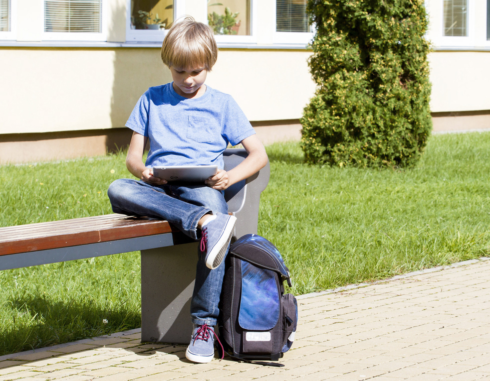 61689745 - schoolboy with tablet pc sitting on the bench near school. outdoor. education, technology people concept