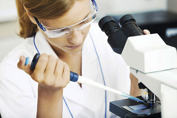 32617623 - beautiful woman in a laboratory working with a microscope.
