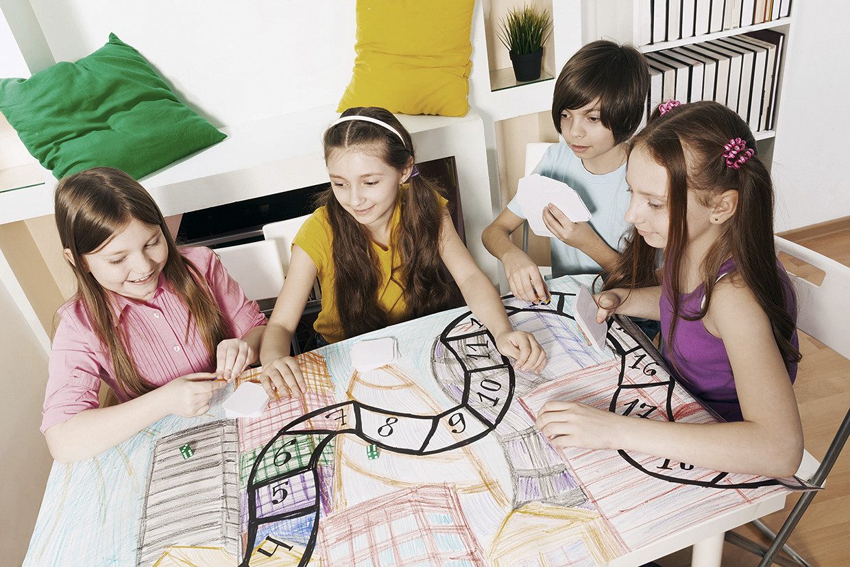 59395960 - top view of four kids sitting at the table, playing the tabletop game with cards
